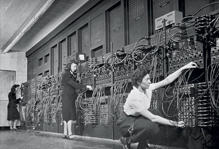 ca. 1940s --- Computer operators program ENIAC, the first electronic digital computer, by plugging and unplugging cables and adjusting switches. | Location: Mid-Atlantic USA.  --- Image by © CORBIS